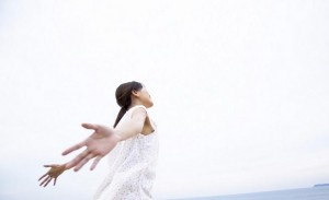 Woman by Ocean with Arms Outstretched